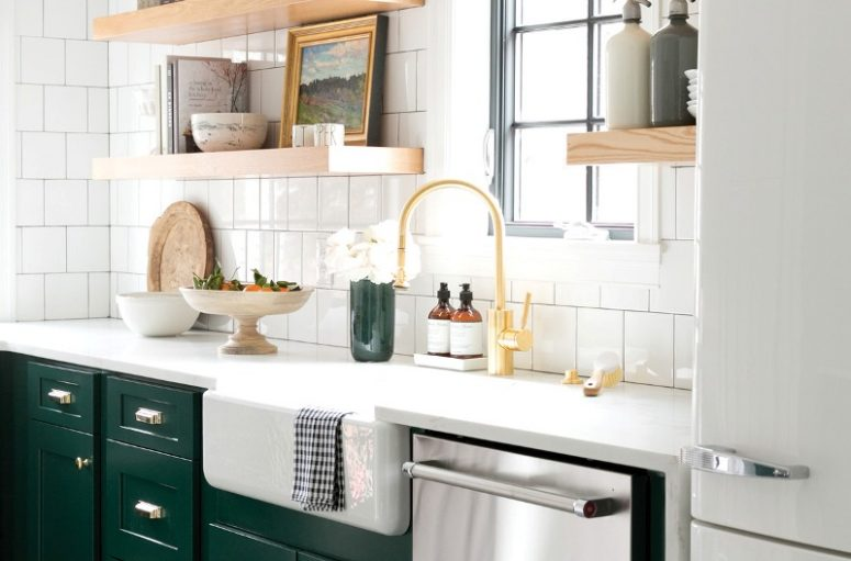 an elegant kitchen with dark green cabinets, chrome appliances, a gold faucet, gold fixtures and open thick shelves and white tiles