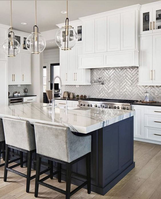 an elegant kitchen with white shaker cabinets, a navy kitchen island with a dining space, chrome fixtures and appliances and gold and glass pendant lamps