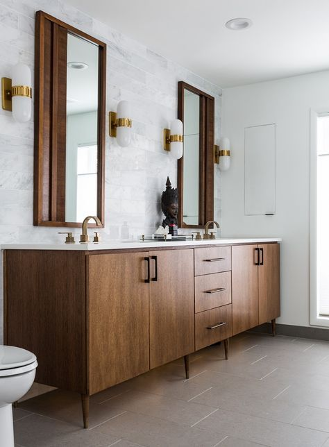 an elegant mid-century modern bathroom with marble and tan tiles, a stained wooden vanity, mirrors in wooden frames and sconces