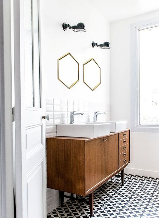 an elegant mid-century modern bathroom with white square tiles and black and white mosaic tiles on the floor, a stained vanity