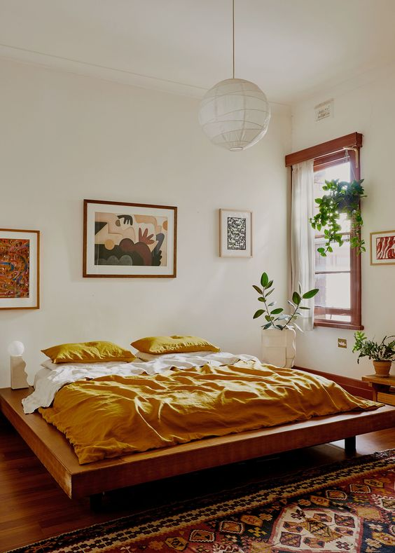 an elegant mid-century modern bedroom with a stained bed with no nightstands, a mini gallery wall, potted plants and bold bedding and a rug