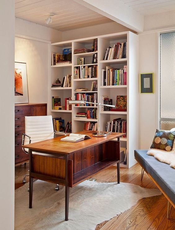 an elegant mid-century modern home office with a large bookcase, a rich-stained desk and a sideboard, a white leather chair and a slate grey sofa