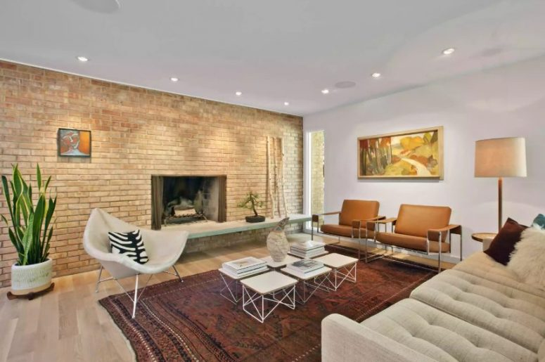 an elegant mid-century modern living room with a brick wall with a fireplace, rust-colored chairs, a white chair and a sofa plus an arrangement of coffee tables