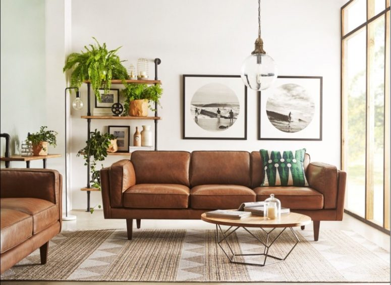 an elegant mid-century modern living room with brown leather sofas, an open shelving unit, a low coffee table and lots of greenery