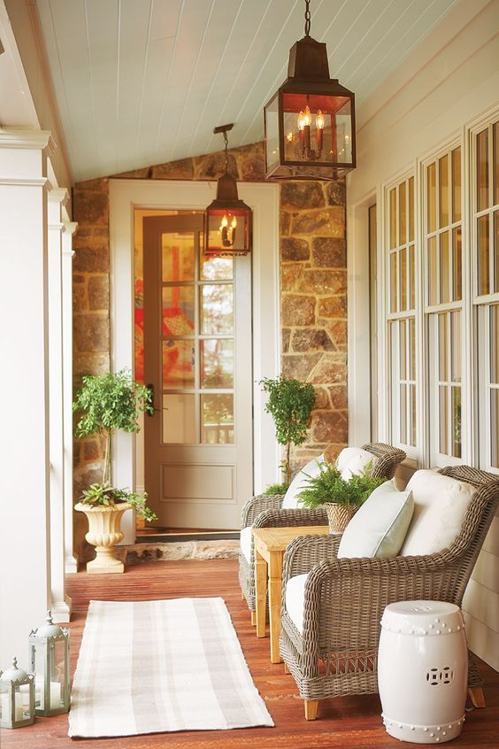an elegant summer porch with wicker chairs and a coffee table, printed textiles, potted greenery and lanterns