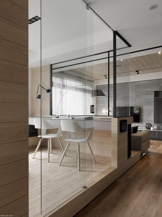 an ethereal glass sliding door separates a shared home office from the rest of the space but still is invisible