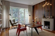 an eye-catchy home office with a stained wood accent wall, a fireplace, a stained desk, red chairs, a bookshelf and lamps