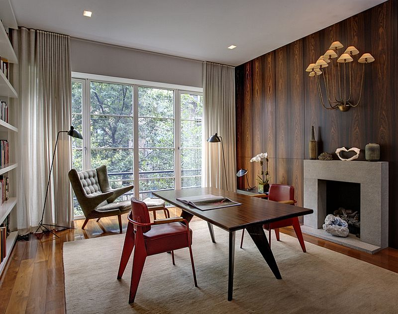 an eye catchy home office with a stained wood accent wall, a fireplace, a stained desk, red chairs, a bookshelf and lamps