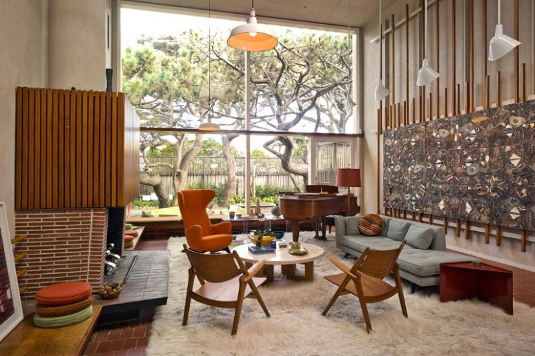 an eye-catchy living room with a fireplace clad with concrete, brick and wood, with a pale blue sofa, an orange chair, wooden chairs and a round table plus a bold artwork