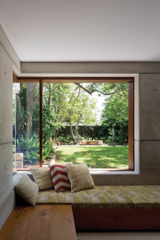 an industrial space with concrete walls, a stained bed and nightstand by a corner window that provides a beautiful view of the garden
