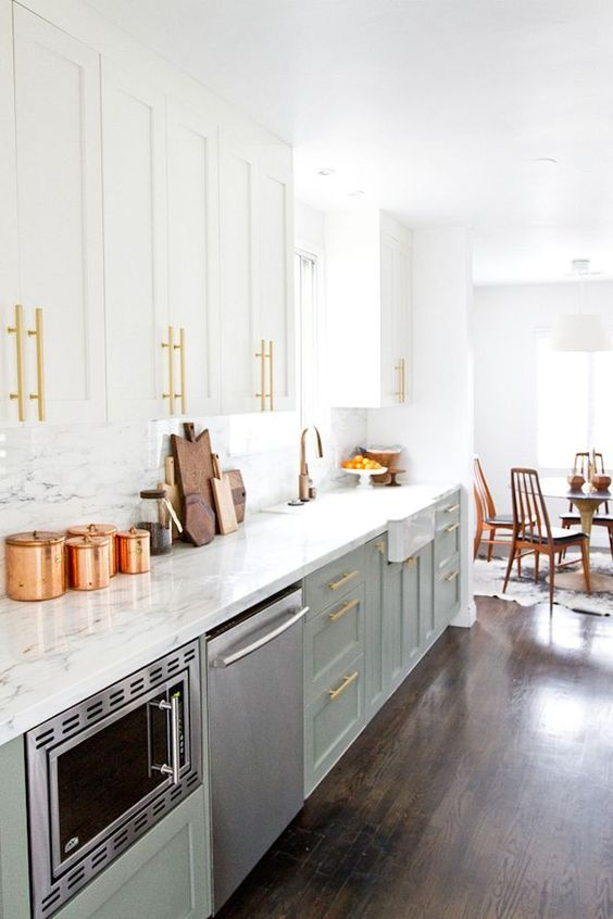 an inviting mid-century modern kitchen with light green and white cabinets, a white stone backsplash and countertops, gold touches