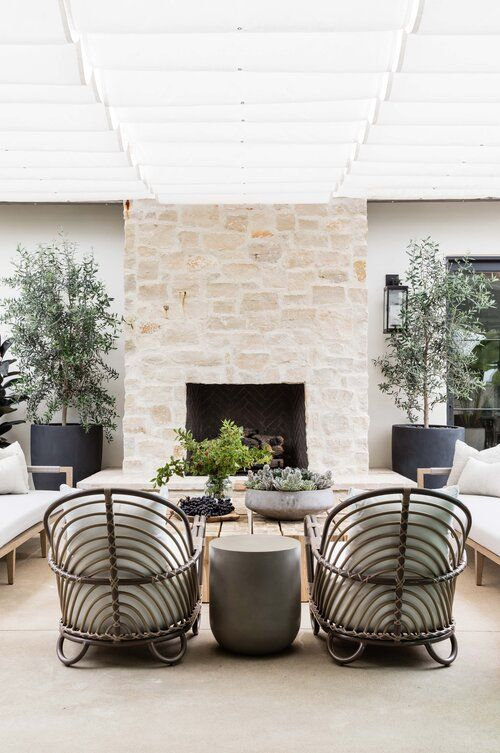 an inviting modern terrace with a large stone clad fireplace, rattan and wood furniture, potted greenery and trees is chic