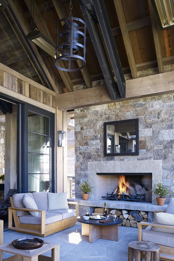 an outdoor space under a roof, with a stone fireplace, neutral modern furniture, metal pendant lamps and a low coffee table is chic