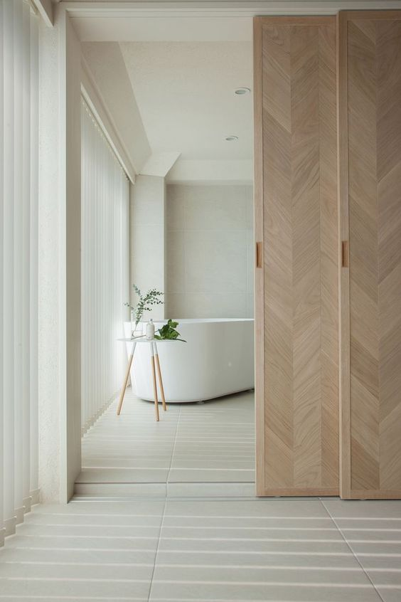 beautiful chevron pattern wooden sliding doors delicately separate the bathroom from the rest of the space and add interest