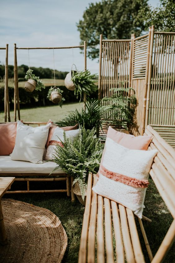 cool and simple bamboo furniture with muted and neutral pillows, a bamboo screen and potted plants for a lovely and welcoming outdoor space