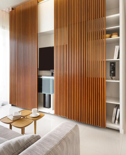 cool rich-stained wood slab sliding doors hide the fireplace, TV and some built-in shelves when they are not in use