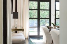elegant dark French doors and windows echo with the dark floor and some other touches in the space, and neutral furniture contrasts them creating a bold look