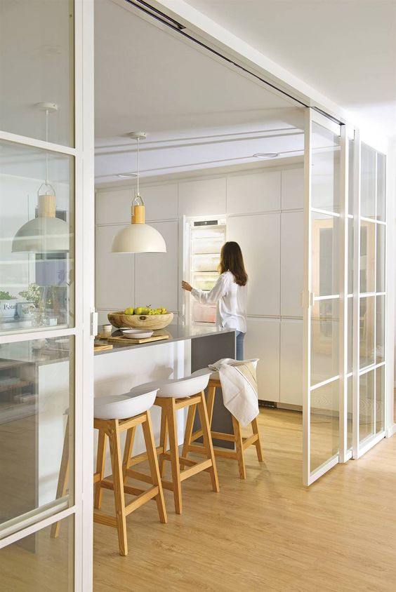 elegant white French sliding doors brilliantly divide the eat-in kitchen and the living room and kitchen gets enough light