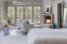 large vintage bedroom with a skylight, a fireplace and a siting zone by it, a bed with neutral bedding, an artwork and a lounger
