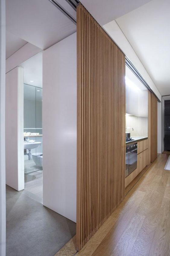light-stained wooden slab sliding doors hide the small kitchen and allow to make the space sleeker and cleaner when the kitchen is not in use
