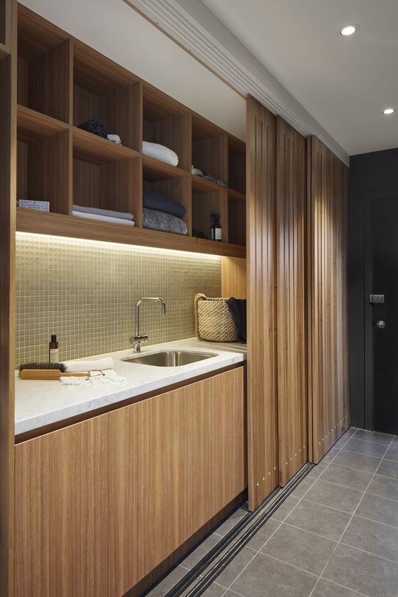modern and sleek wooden sliding doors that hide the kitchen in an open layout are a very chic and cool idea