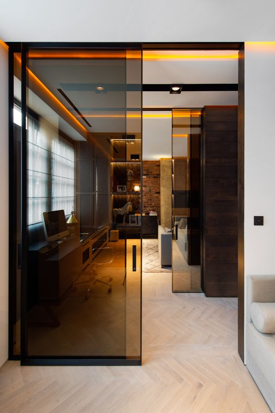 modern black glass sliding doors that separate the home office from the rest of the space in a delicate and very stylish way