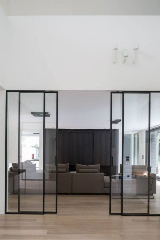 modern glass and black framing sliding doors delicately separate the spaces and let light in and out