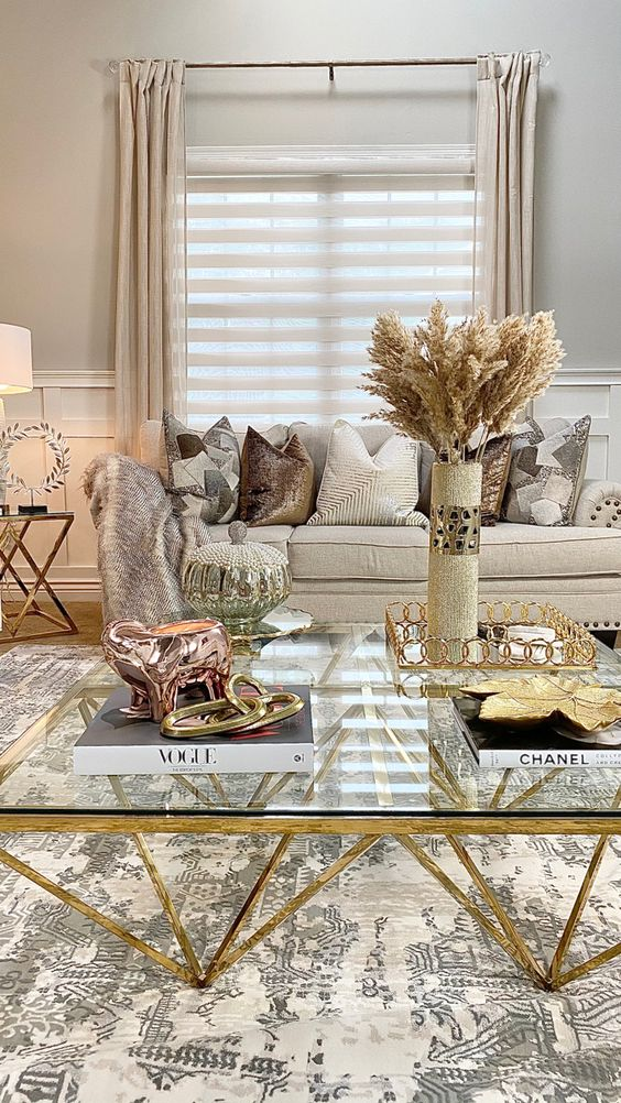 pretty living room decor done with metals and sparkles for a glam feel - a coffee table with gold legs, a gold tray, a copper and gold decoration and some sparkling pillows