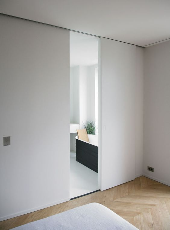 sleek and minimalist white sliding doors that look like a wall and separate the bathroom from the bedroom