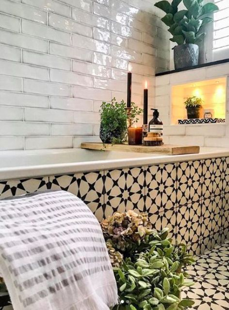 a beautiful bathroom with white tiles and bold navy Moroccan tiles covering the floor and the bathtub, a niche with lights and potted greenery