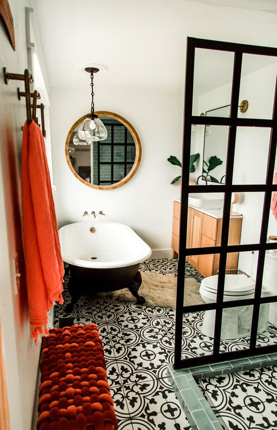 a beautiful eclectic bathroom with white walls, black and white Moroccan tiles, a black clawfoot tub, a neutral vanity, a black glass shower wall, a bold pompom bench