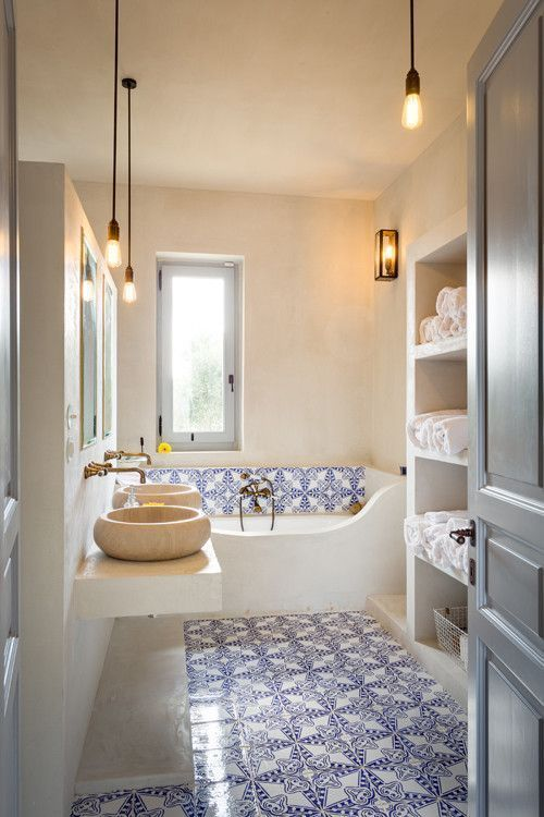 a beautiful Moroccan-inspired bathroom accented with blue Moroccan tiles, hanging bulbs and a storage unit plus an airy vanity