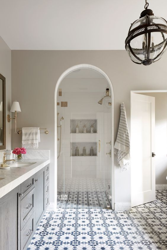 a beautiful neutral bathroom with blue Moroccan tiles on the floor, a grey vanity, a sphere chandelier, a shower space with built-in shelves