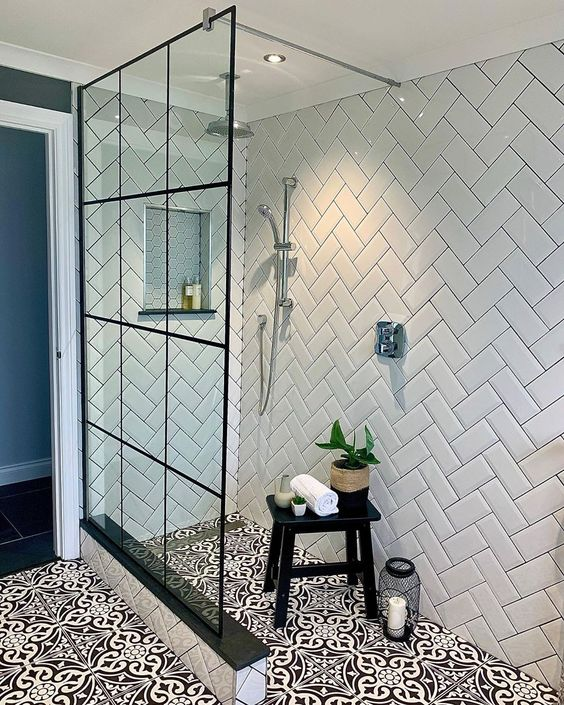 a black and white bathroom with white chevron tiles on the walls, black and white Moroccan tiles on the floor and a glass shower wall