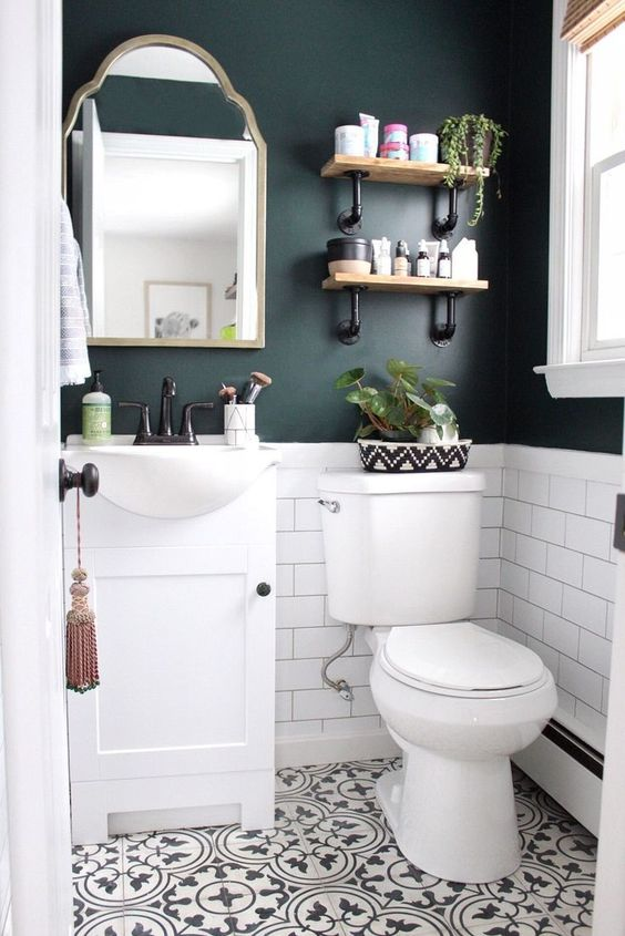 a black and white powder room with black walls, white subway tiles, Moroccan tiles on the floor, a white vanity and white appliances