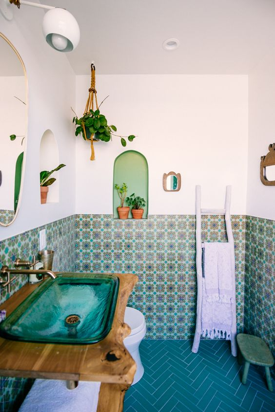 a bright bathroom with colorful Moroccan tiles and blue chevron tiles on the floor, a turquoise glass sink and potted plants