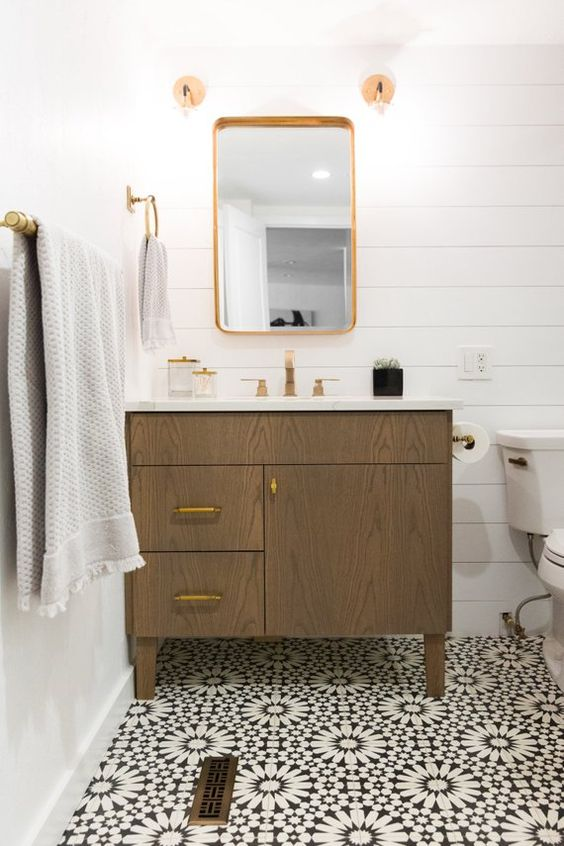 a chic bathroom with white plank walls, a Moroccan tile floor, a stained vanity, gold fixtures and neutral textiles is a lovely space