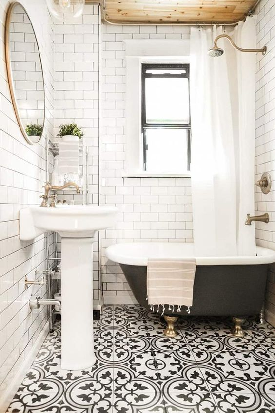 a chic farmhouse black and white bathroom with white subway tiles, Moroccan tiles on the floor, a black soak tub, a round mirror and potted greenery