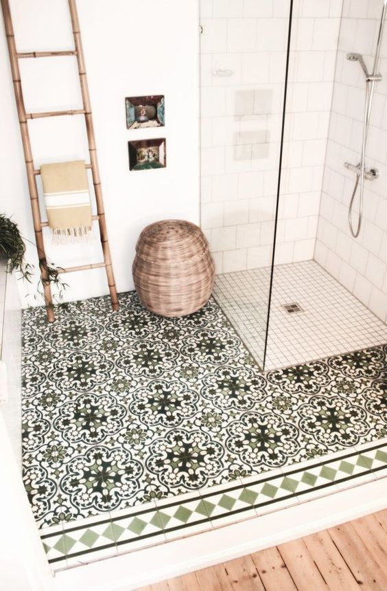 a cozy bathroom clad with white subway and smaller scale tiles, with green Moroccan tiles, a bamboo ladder, a basket for storage is cool