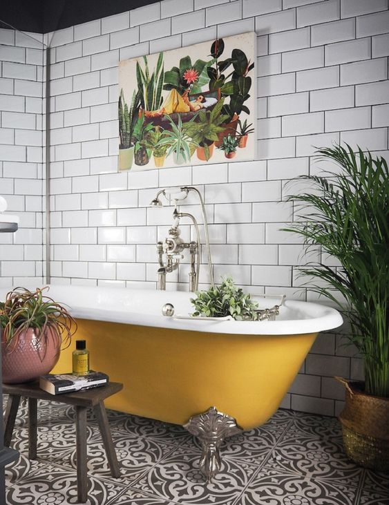 a pretty bathroom with white subway tiles, black and white Moroccan ones on the floor, a mustard vintage tub, potted plants is a chic idea