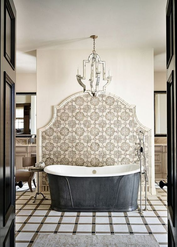 a refined bathroom with geo and Moroccan tiles, a metal clad bathtub, a mirrored chandelier and some neutral furniture