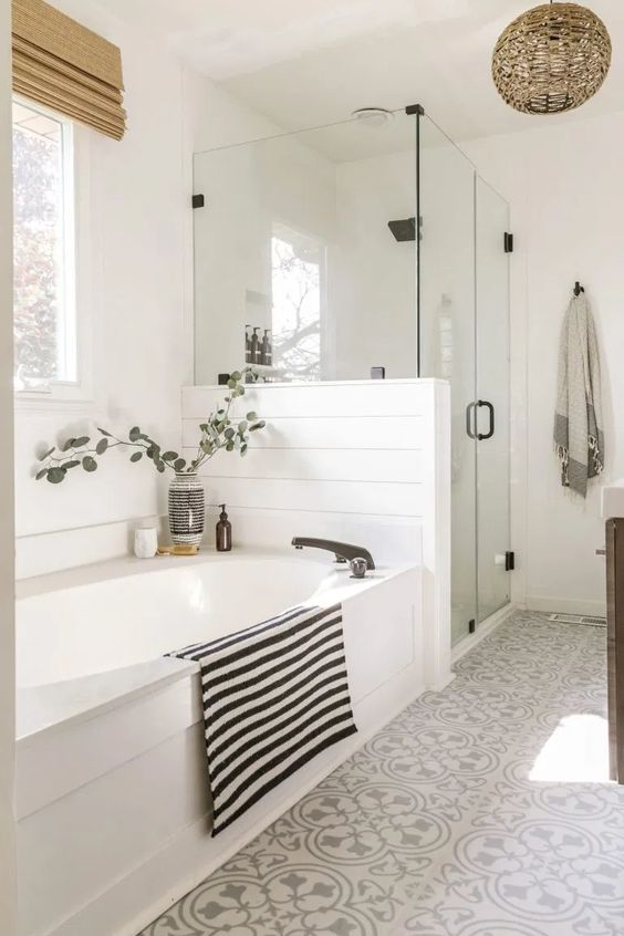 a serene farmhouse bathroom with white planked walls, grey and white Moroccan tiles, a bathtub covered with white panels, a woven lamp