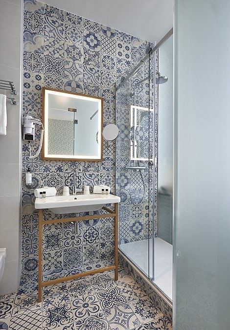a small and chic contemporary bathroom with blue Moroccan tiles all over, a sink stand and a mirror in a gidled frame with lights