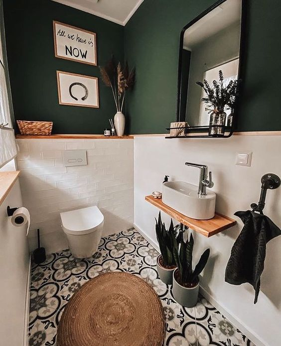 a small and chic powder room with green walls and white tiles, pretty Moroccan tiles on the floor, white applainces and some potted plants
