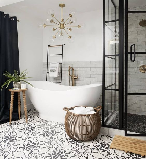 a stylish bathroom with marble and Moroccan tiles, a vintage tub, a shower space with framed glass walls, a gilded chandelier and a basket
