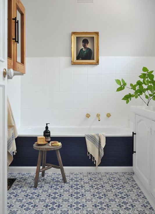 a stylish modern bathroom with blue Moroccan tiles, a bathtub clad with navy tiles, a cabinet, an artwork and a white vanity