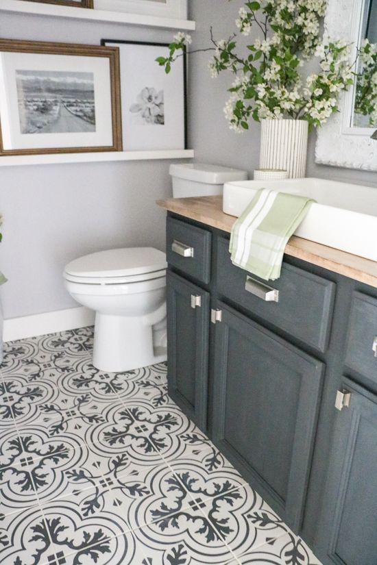 a stylish powder room with a Moroccal tile floor, a graphite grey vanity with a butcherblock countertop, a sink, ledges with artworks