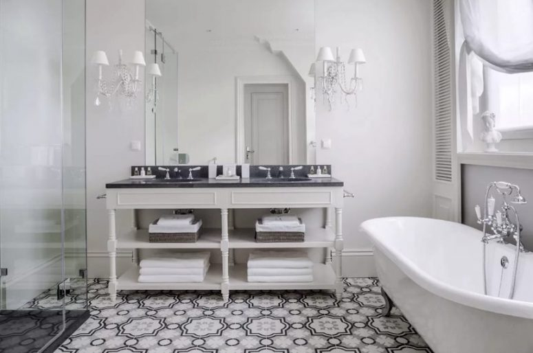 a vintage black and white bathroom with a neutral vanity, black countertops, a shower space, a vintage tub, vintage sconces and shutters on the wall