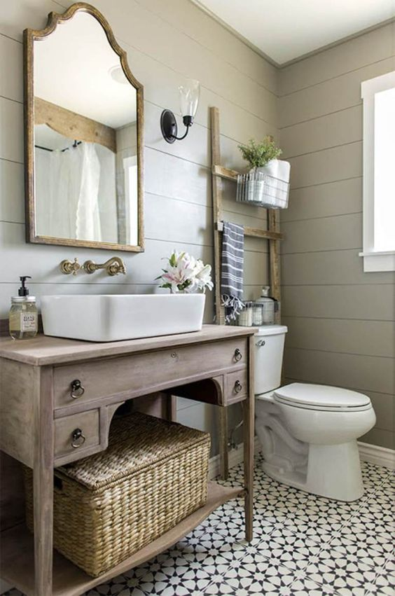 a welcoming farmhouse bathroom with grey planked walls, a Moroccan tile floor, a wooden vanity, a mirror in a wooden frame