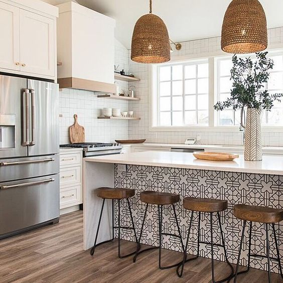 a beautiful farmhouse kitchen with white cabinets and a kitchen island accented with Moroccan tiles, woven pendant lamps, wooden stools and white tiles on the walls